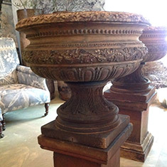 A pair of beautifully decorative buff terracotta pedestal urns
